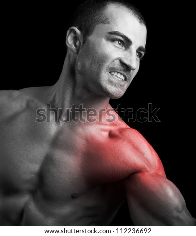 Muscular man suffering with shoulder pain on black background - stock photo