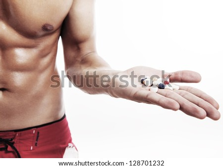 muscular man torso with hand full of pills on white - stock photo