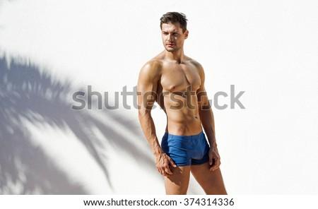 Muscular man wearing blue beach shorts and posing - stock photo