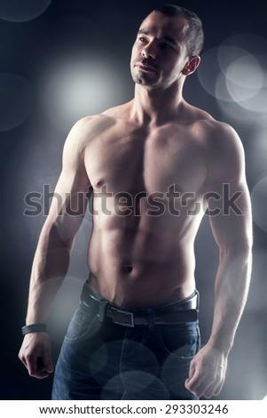 Muscular man wearing fashionable jeans posing in studio shirtless. - stock photo