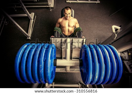 Muscular man weightlifter doing leg presses in gym. Sports. - stock photo