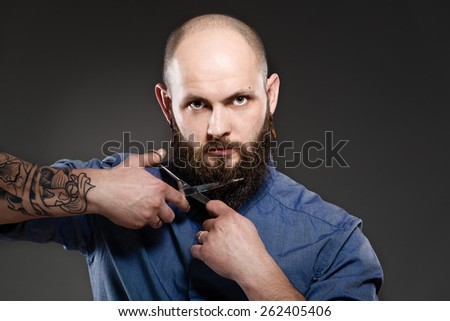 Muscular man with a beard cuts his beard with scissors. He is dressed in a blue shirt. Has a tattoo on his hand. Looking at camera