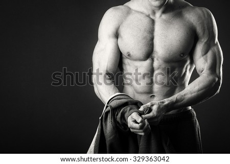 Muscular man with a towel on a dark background. The athlete after a grueling workout. Photos for sporting magazines and websites.