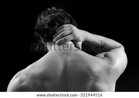 Muscular man with back pain, Black Background - stock photo