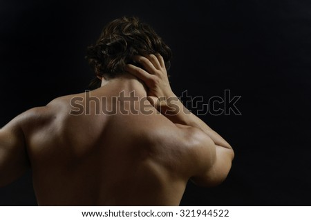 Muscular man with back pain, isolated - stock photo