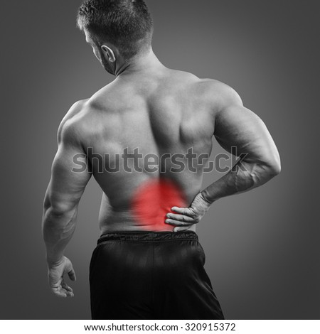 Muscular man with back pain over gray background. Concept with highlighted glowing red spot. - stock photo