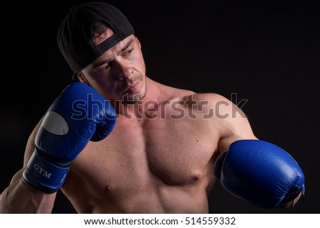 muscular man with  beard in blue boxing gloves
