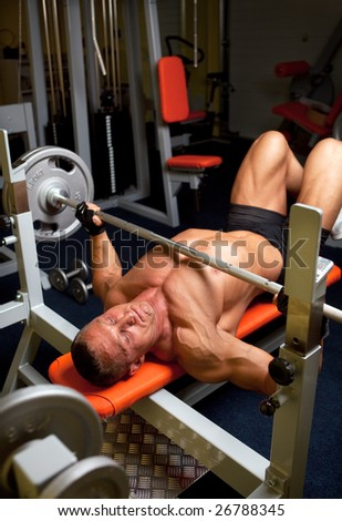 Muscular man with dumbbell in home fitness - stock photo