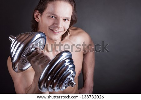 Muscular man with dumbbells on black background - stock photo