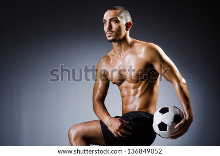Muscular man with football ball