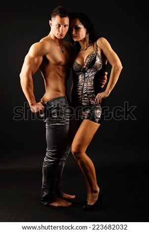 Muscular man with his girlfriend standing on dark background