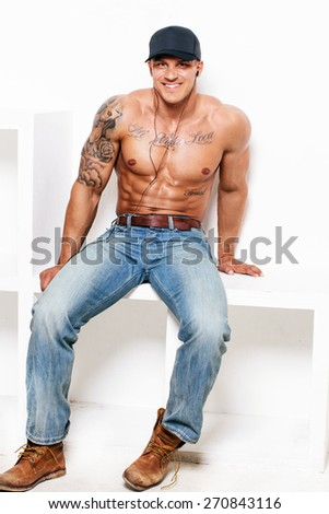 Muscular man with naked torso in blue jeans on white background - stock photo