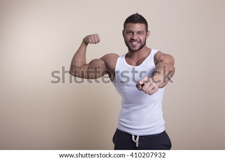 muscular man with perfect body posing in a white shirt on a light background