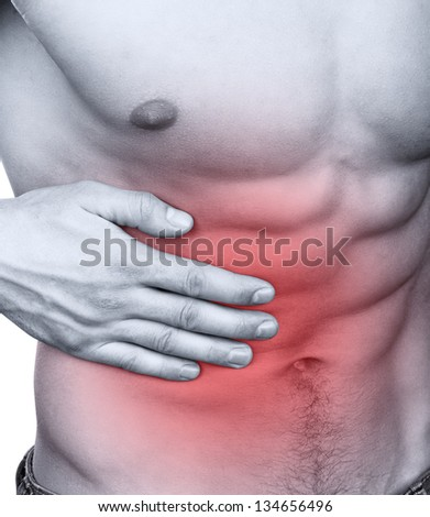 Muscular man with stomach pain isolated on white background - stock photo