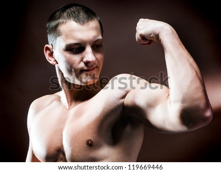 Muscular man with strong biceps on a brown background - stock photo