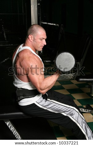 muscular man with tatoos working out in gym - stock photo
