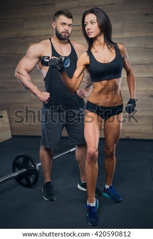 Muscular man with tattoos and beard and beauty girl posing in gym