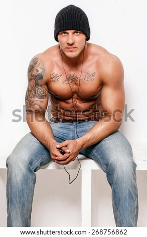 Muscular man with tattos in blue jeans on white background - stock photo