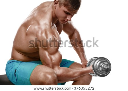 Muscular man working out doing exercises with dumbbells at biceps, strong male naked torso, isolated over white background - stock photo