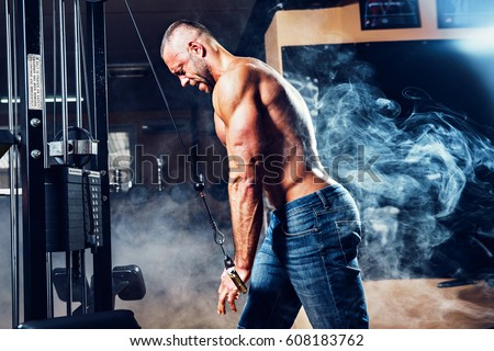 Muscular man working out in gym doing exercises at triceps, strong male naked torso abs. Smoke on background
