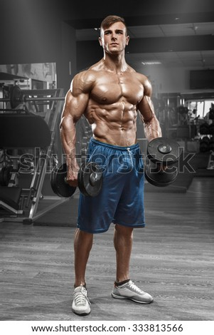 Muscular man working out in gym doing exercises with barbell, strong male naked torso abs - stock photo
