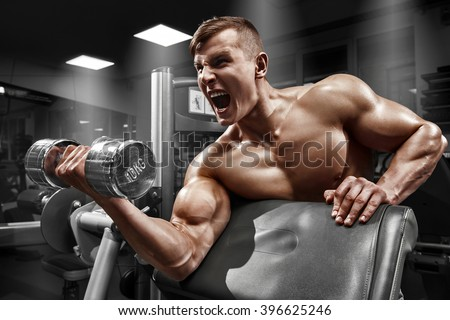 Muscular man working out in gym doing exercises with dumbbell at biceps, strong male naked torso abs - stock photo