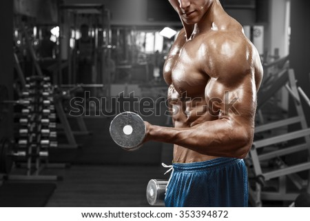 Muscular man working out in gym doing exercises with dumbbells at biceps, strong male naked torso abs - stock photo