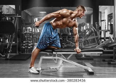 Muscular man working out in gym doing exercises with dumbbells at triceps, strong male naked torso abs - stock photo