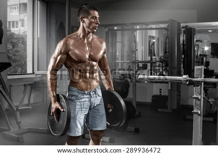 Muscular man working out in gym with barbell, shaped abdominal. Strong male naked torso abs - stock photo