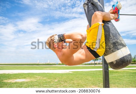 Muscular man working out on punching bag  - stock photo