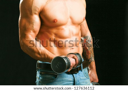 Muscular man working out with dumbbells over black background - stock photo