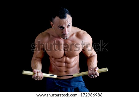 Muscular martial arts man shirtless using nunchuks, isolated on black background
