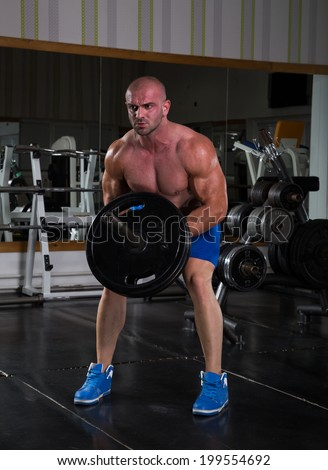 Muscular men exercising with weights. He is performing T bar rows for back muscle / Bodybuilder in the gym - stock photo