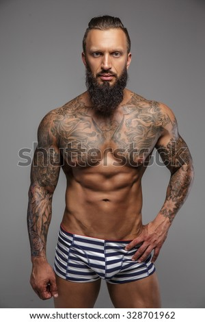 Muscular nude man with tattooed body isolated on grey background.