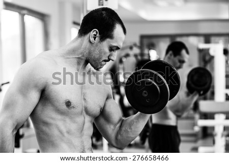 Muscular power athletic male bodybuilder sitting and training his biceps with dumbbells in fitness center. Black and white photo - stock photo
