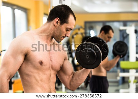 Muscular power athletic male bodybuilder training his biceps with dumbbells in fitness center - stock photo