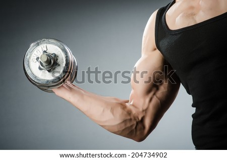 Muscular ripped bodybuilder with dumbbells - stock photo