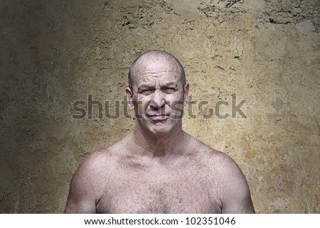 Muscular scowling man in aggressive posture in front of a concrete wall - stock photo