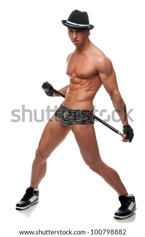 Muscular sexy naked man dancing in the studio in underwear, hat and gloves with a cane - stock photo