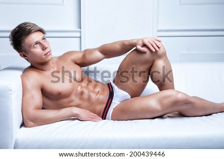 muscular sexy young naked athlete lying on the sofa in underwear