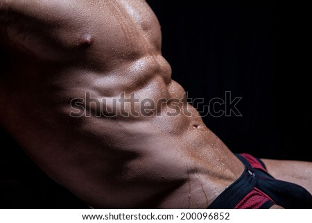 Muscular sexy young naked wet male torso in underwear - stock photo