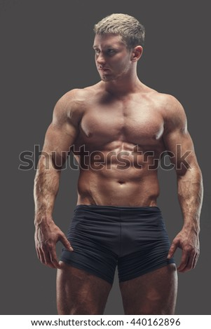 Muscular shirtless athlete in black panties isolated on grey background.