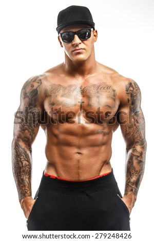 Muscular shirtless macho man with tattooes posing in studio on white background