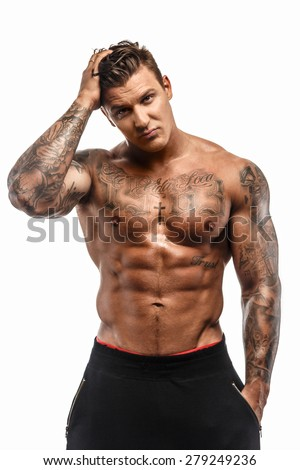 Muscular shirtless macho man with tattooes posing in studio on white background - stock photo