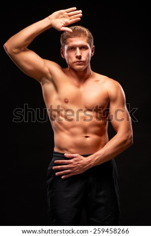 Muscular shirtless sportsman looking at camera with raised hand, demonstrating biceps, triceps, pectoral and abdominal muscles, dressed in black shorts, isolated on black background - stock photo