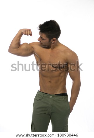 Muscular shirtless young man flexing and looking at his own bicep, isolated on white - stock photo