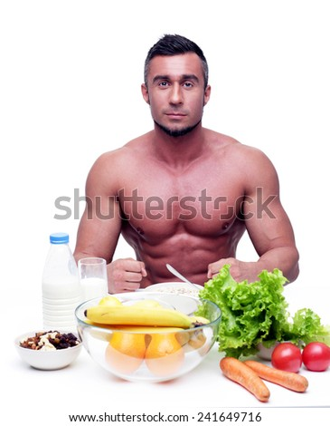 Muscular sports man sitting at the table with healthy food - stock photo