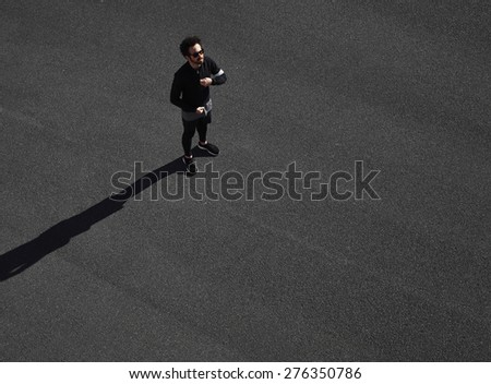 Muscular sportsman model ready for his run on a black asphalt. Fit strong man on his mark to start running. Determined athlete outdoors.  - stock photo