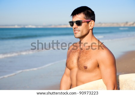 Muscular surfer wearing sunglasses and holding his surf board overlooking the ocean. - stock photo
