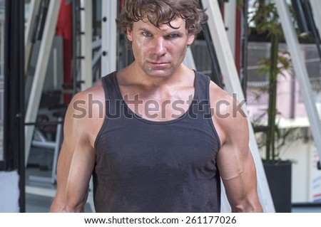 Muscular sweaty Caucasian man with intense expression looking at camera and wearing tank top in gym - stock photo